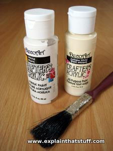 Two pots of acrylic paint next to a paintbrush