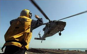 A landing signal enlisted (LSE) guides a helicopter safely in to land on the deck of an aircraft carrier.