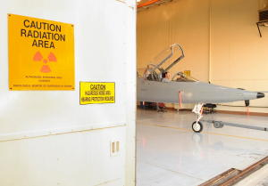 Nondestructive testing an airplane with X rays in a lead-lined hangar.