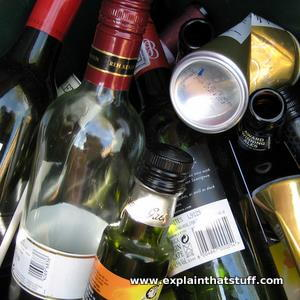 Generic illustration of alcohol abuse: bottles and cans in a recycling dumpster