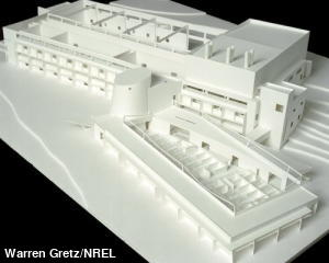 Architectural model of a building made from white cardboard.