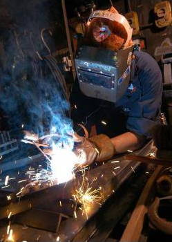 Someone arc welding with sparks flying and goggle mask