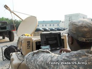A US army soldier makes a VoIP call from a laptop connected via a radar dish to a satellite.
