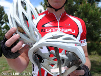 The smashed remains of a damaged helmet with a cyclist in a red jersey holding them in his hands.