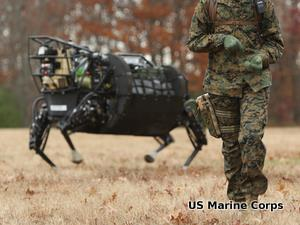 Military Big Dog robot running through a field alongside a soldier.