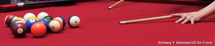 A billiard cue, balls, and table.