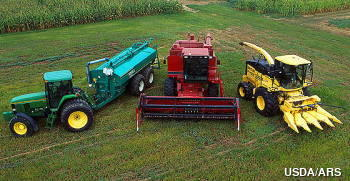 Three large agricultural farm machines together in a field