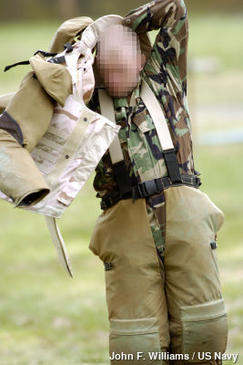 Photo of solider putting on energy-absorbing military body armor.