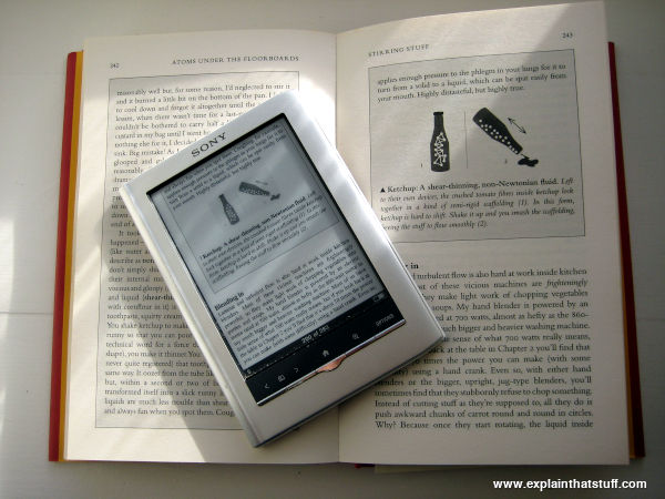 A Sony Reader laid on a hardback book to show the difference in page size
