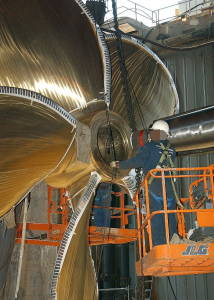 A shiny new brass ship propeller with a worker alongside for scale.
