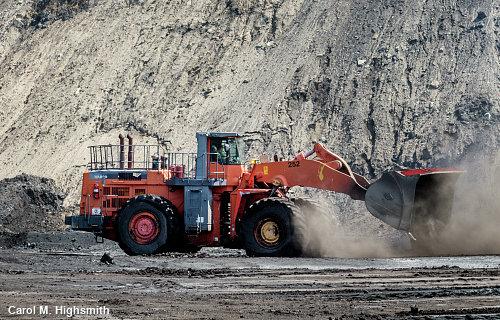 Photo of orange bulldozer in a mine.