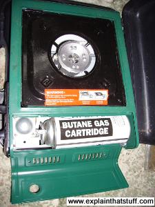 Green portable camping stove with a white butane gas cylinder.