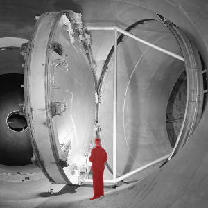 A large open butterfly valve in a wind tunnel with a man standing next to it.