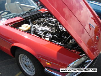 a red jaguar xjs sports car with the bonnethood open