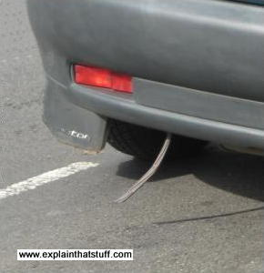 Anti-static strip hanging from the back of a car