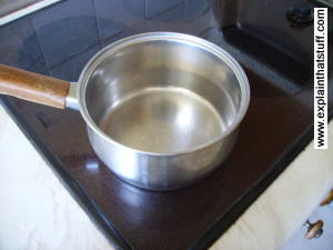 A metal saucepan sitting on a ceramic/glass cooktop.