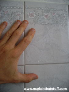 Gray ceramic wall tiles with a man's left hand for scale