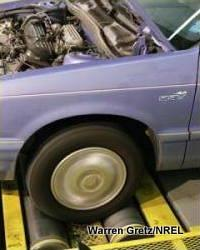 Photo showing a car's front wheels turning a chassis dynamometer's rollers.