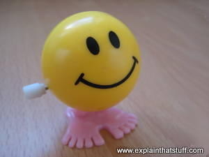 A yellow clockwork windup toy with a smiling face.
