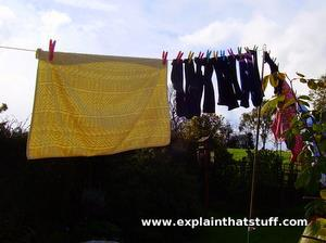 Clothes on an outdoor washing line propped high off the ground to make them dry more quickly.