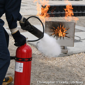 Military firefighter using a carbon dioxide extinguisher to put out a fire