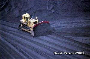 Photo of bulldozer moving coal at an electricity generating power plant.