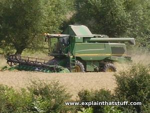 Side view of a green John Deere combine harvester cutting corn.