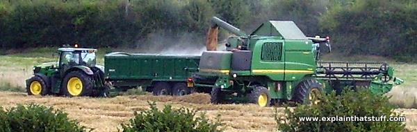 Unloading grain from a combine harvester with a tractor and trailer alongside.