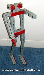 A grey and red plastic humanoid robot built with a construction set.