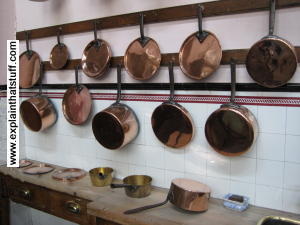 Copper cooking pans hanging up on a rack in the wall of a kitchen.