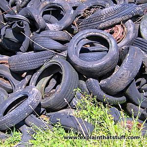 A heap of worn out, discarded rubber car tires piled on top of grass.