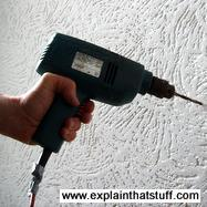Drilling into a wall with a blue electric cordless drill.