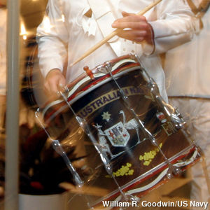A marching navy drummer hits a drum with his sticks