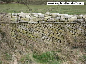 Dry stone wall built on an incline with stones at an angle.