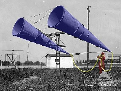 A airman uses giant ear trumpet amplifiers listening out for approaching airplanes at Bolling Field in 1921.