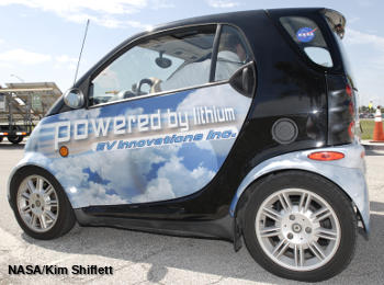 An electric Smart Car with a sticker reading Powered by Lithium