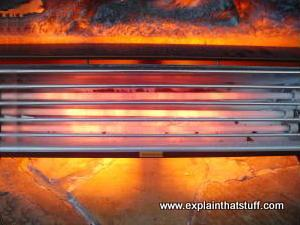 An electric radiator, with glowing red heating elements, on a stone hearth.