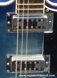 A closeup of the electromagnetic pickups under the strings of an electric guitar.