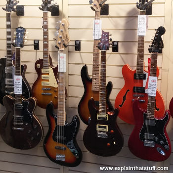 A display of electric guitars hanging up in a store window.