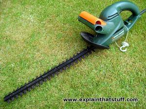 Black and Decker green electric hedge cutter.