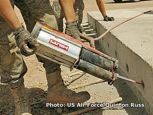 Applying epoxy sealant to a concrete wall using a pneumatic dispenser.