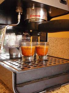 Rich coffee pours from the spout of an espresso machine