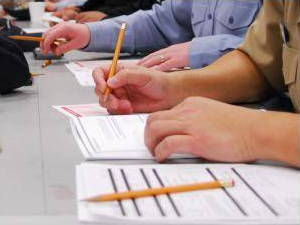 Examination papers on a desk. Closeup of students' hands holding pencils over papers.
