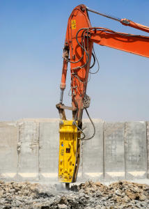 A yellow jackhammer mounted on an excavator, breaking up rubble.