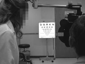 A patient reading a Snellen optician's eye examination chart with letters in rows that get smaller and smaller.