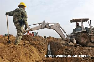 An excavator digs a trench for a fiber optic cable.