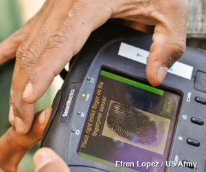 A person has their fingerprint taken with an electronic scanner