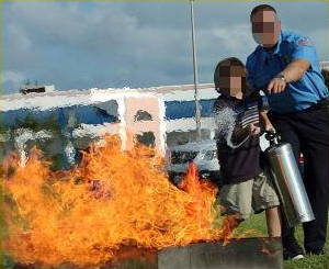 A boy being taught how to use a fire extinguisher on a blazing fire