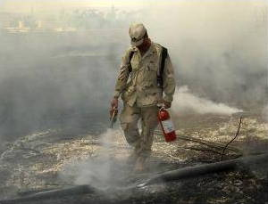 Military firefighter using an extinguisher to put out a fire
