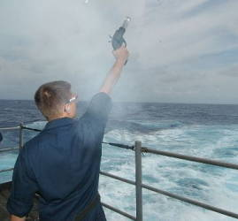 Firing a flare gun from a ship.